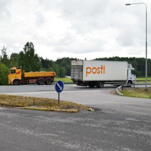 En gul lastbil möter en vit Posti-lastbil i en asfalterad vägkorsning. I förgrunden syns ett stopmärke och i bakgrunden skog och en väg.