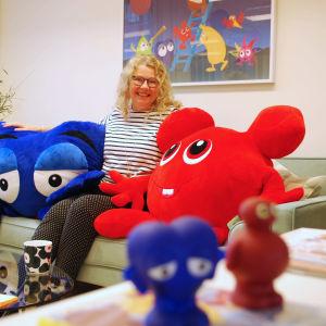 Anneli Tisell sitter i en soffa med två stora figurer från Babblarna.