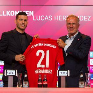 Lucas Hernandez och Karl-Heinz Rummenigge håller upp en speltröja.
