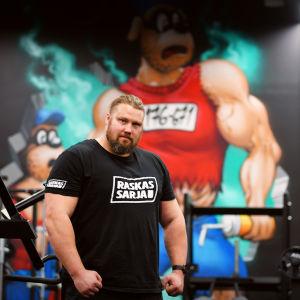 Mika Törrö spänner musklerna framför en graffiti med muskulösa Björnligan som motiv