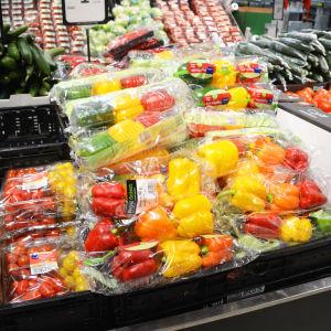 En hylla med gula, röda och gröna paprikor och tomater i plastpåsar.