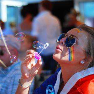 Michelle Wanström blåser såpbubblor inför starten till Åland Pride-paraden.