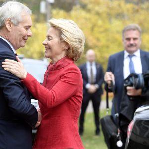 En brett leende Antti Rinne skakar hand med en leende Ursula von der Leyen i förgrunden, kostymbeklädda män står i bakgrunden.