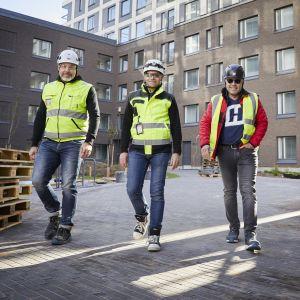 Kolme valkokypäräistä ja keltaliivistä miestä kävelee kerrostalon pihalla rinnakkain.