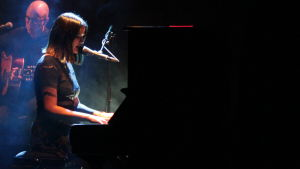 En mörkhårig kvinna spelar piano