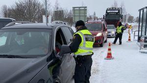 Gränsbevakningens tjänstemän granskar bilar i en kö.