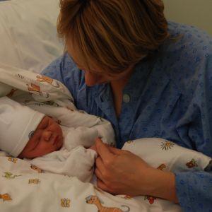 Nyfödd i famnen inlindad i en filt.