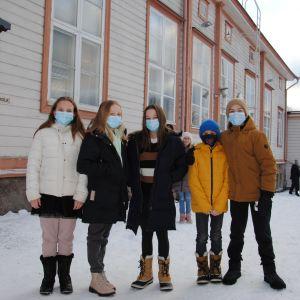 Fem barn med munskydd står på snöig skolgård.