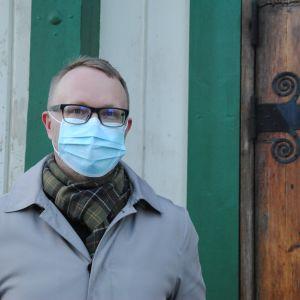 Man med grönrutig halsduk, glasögon, munskydd, ljust kort hår och och beige rock står utanför gammal trädörr.