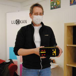 Man med kort ljusbrunt hår och svart tröja står visar upp en kamera byggd av legobitar.