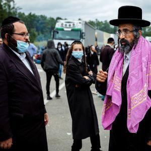Joukko hasidijuutalaisia seisoo tiellä. Taustalla näkyy jono kuorma-autoja.