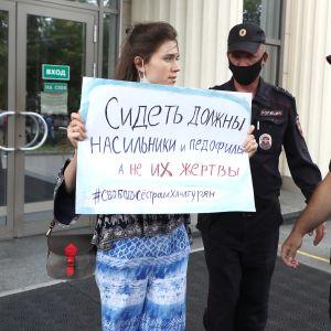 En demonstrant håller upp ett plakat. Två vakter står bredvid henne