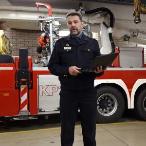 Pelastuspäällikkö seisoo paloauton edessä.