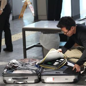 En man tar ut sin bärbara dator ur en kappsäck på golvet på Ataturk Airport, i Istanbul.