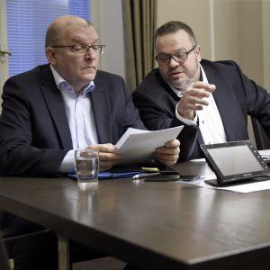 Riku Aalto och Toni Laiho sitter vid riksförlikningsmannens bord och tittar på papper.