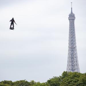 En man flyger på en flygbräda bredvid Eiffeltornet.