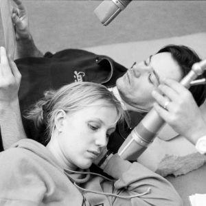 Arja-kuunnelman pääosan esittäjät Merja Larivaara ja Carl-Kristian Rundman äänittävät roolejaan ja makoilevat radiostudion lattialla.