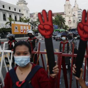 Kolmen sormen -kyltit työjen käsissä Myanmarissa.