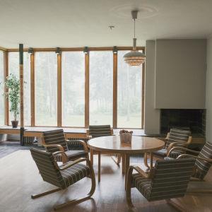Artek-kalusteista koostuva tuoliryhmä, taustalla suuret ikkunat.