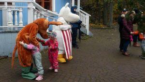 Två barn kramar Sniff i Muminvärlden i Nådendal.