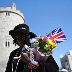 En person med solglasögon bär på en brittisk flagga och gula och rosa blommor.