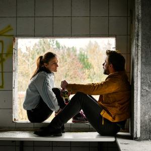 Martin & Anna / Anders Juul & Marijana Jancovic sitter i fönster i övergivet hus.