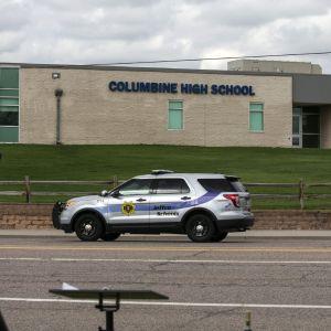 En bild på Columbine High Schools sandfärgade byggnad. På vägen framför byggnaden kör en polisbil förbi.