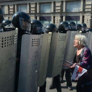 En dam talar med poliser som bevakar demonstration i Minsk 30.8.2020