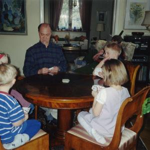 Isoisä, Jussi Huttunen, pelaa korttia lastenlasten kanssa.