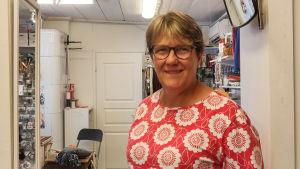 En leende kvinna står inne i en hantverksaffär.