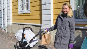 En ung kvinna står och håller i handtaget till en barnvagn. Bakom henne synns en gul husvägg.
