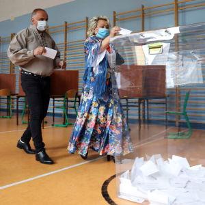 Nainen tiputtaa äänestyslipukkeen äänestysastiaan presidentinvaalin toisen kierroksen äänestyksessä Puolassa 12. heinäkuuta.