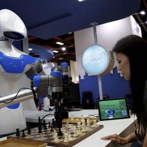 En vit robot spelar schack med en kvinna.
