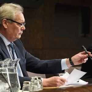 En glasögonprydd och kostymklädd Antti Rinne sitter i profil framför en mikrofon.