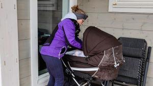 En kvinna i lila jacka sköter om en baby som ligger i en barnvagn.