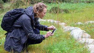 Kajsa Rosqvist sitter på huk i gräset och tar ett foto med mobiltelefonen.