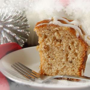 Kuivakakusta palanen valkoisella lautasella, jossa myös kakkuhaarukka. Taustalla hopeanvärinen joulukoriste.