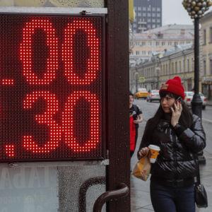 En kvinna passerar en skylt med rubelns valutakurs.