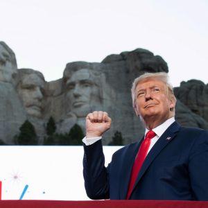 Trump i kostym gör en knytnävsgest med ena handen framför Mount Rushmore.