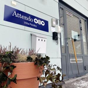 En ingång till en byggnad. På en skylt vid sidan om ingången står det Attendo Villa Pentby.