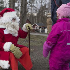 Joulupukki juttelee pikkutytölle.