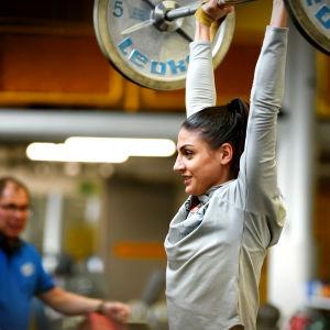 Nootalotta Neziri i gymmet med stången på raka armar ovanför huvudet
