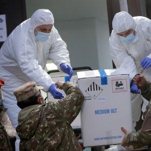 Soldater lyfter upp en låda med coronavaccin åt två personer i skyddsutrustning som tar emot lådan.