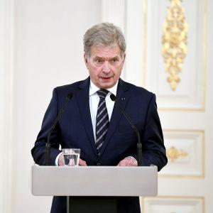 En gråhårig man står vid ett podium och talar.