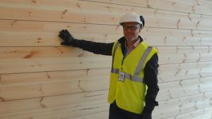 Timo Tenhunen tar med handen på en stockvägg i en ny skola