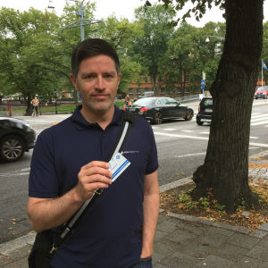 Mathias Johnson står vid gatan och håller upp sitt busskort.