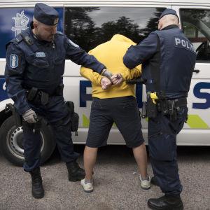 Poliisit laittavat käsirautoja pidätetyn käsiin.