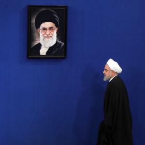 Irans president Hassan Rouhani går förbi ett foto på den högsta ledaren Ali Khamenei