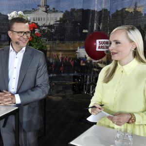 Samlingspartiets ordförande Petteri Orpo och De grönas Maria Ohisalo står bredvid varandra inför debatt.