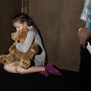 En liten flicka kurar rädd i hop sig med mjukisnalle i ett hörn. I förgrunden en manshand med en vinflaska.